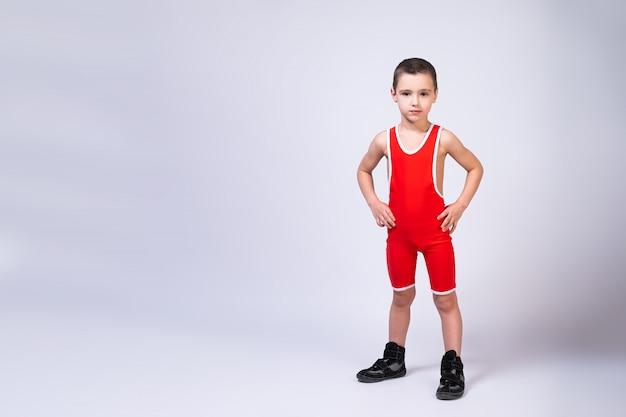 Das porträt eines kleinen fröhlichen jungen in einer roten wrestling-strumpfhose hält seine hände auf den seiten, schaut selbstbewusst in die kamera und posiert auf einem weißen einzelgänger