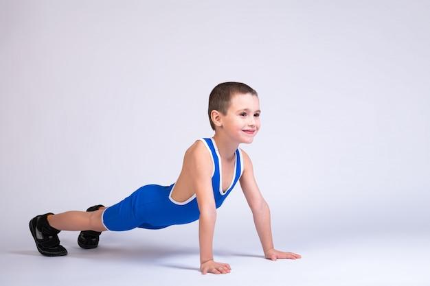Das porträt eines kleinen jungen in einer blauen wrestling-strumpfhose und p steht in einer push-up-pose auf seinen händen, schaut nach vorne und posiert auf einer weißen isolation