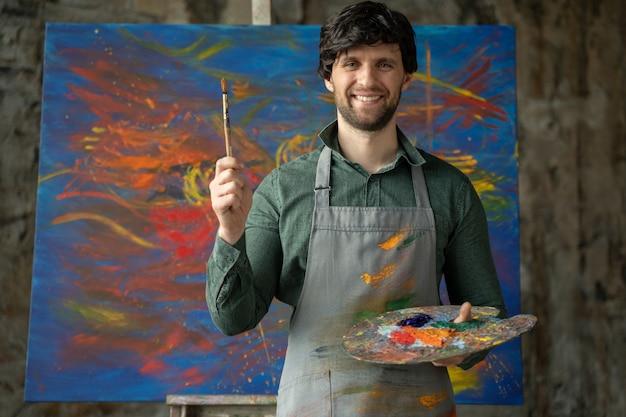 Das porträt eines männlichen künstlers hält einen pinsel