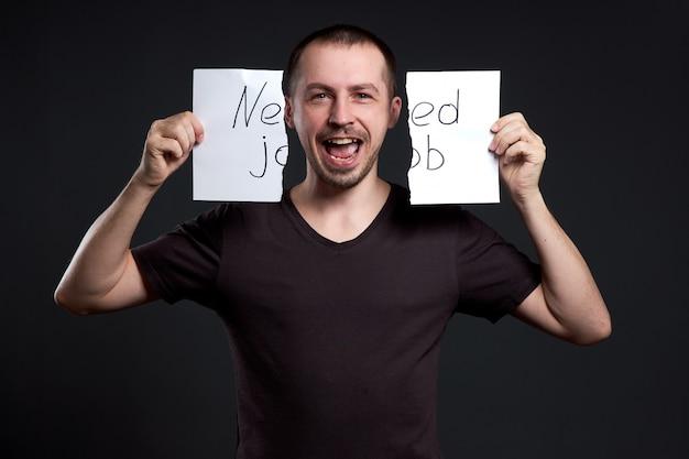 Das porträt eines mannes, der eine inschrift auf papier zerreißt, braucht einen job