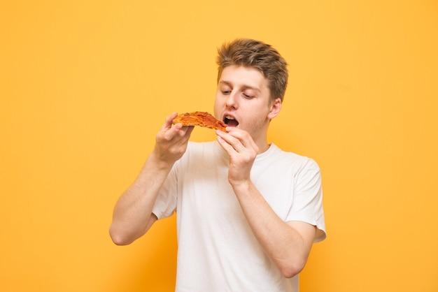 Das porträt eines mannes in einem weißen t-shirt hält ein stück pizza in seinen händen
