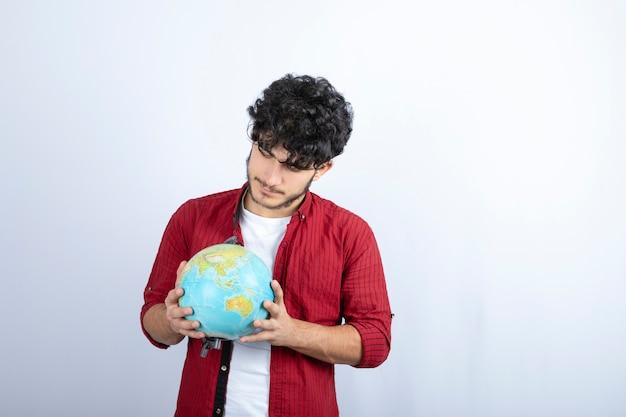 Das porträt eines nachdenklichen bärtigen mannes will unbekannte orte erkunden und schaut auf den weltweiten globus.