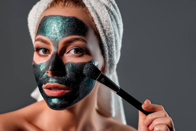Das porträt eines schönen mädchens legt eine grüne peel-off-maske auf ihr gesicht. grauer hintergrund. schönheitsgesichtspflege für mädchen. kosmetik-, beauty- und spa-konzept.