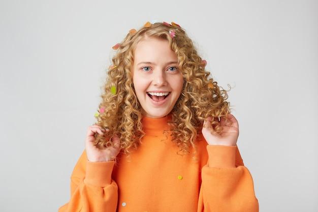 Das porträt eines sehr glücklichen mädchens im orangefarbenen pullover berührt spielt mit ihrem lockigen haar und lächelt isoliert auf einer weißen wand