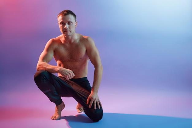 Das porträt eines sportlers, der gegen neonraum hockt, schwarze hosen trägt, oben ohne und barfuß posiert, seine perfekten formen zeigt, schaut in die kamera.