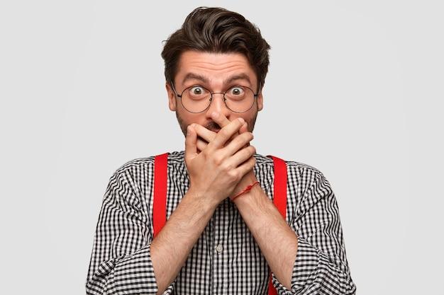 Das porträt eines überraschten jungen mannes bedeckt den mund, versucht kein geheimnis zu verraten und verbreitet gerüchte, hat einen mysteriösen ausdruck