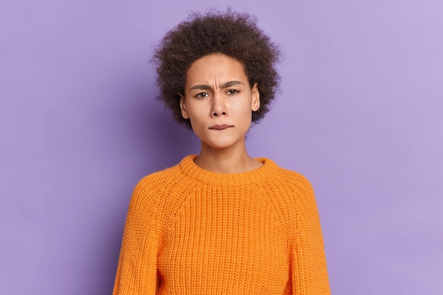 Das porträt eines unzufriedenen dunkelhäutigen mädchens mit lockigem haar beißt die lippen und runzelt die stirn. das gesicht sieht missfallen aus, gekleidet in einen gestrickten orangefarbenen pullover.