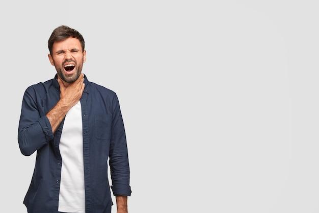 Das porträt eines unzufriedenen mannes fühlt schmerzen, hat einen kranken hals, kann nicht laut sprechen, hat asthmaanfall