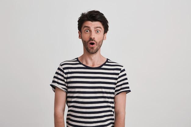 Das porträt eines verblüfften attraktiven jungen mannes mit borsten und geöffnetem mund trägt ein gestreiftes t-shirt und fühlt sich über der weißen wand isoliert und schockiert