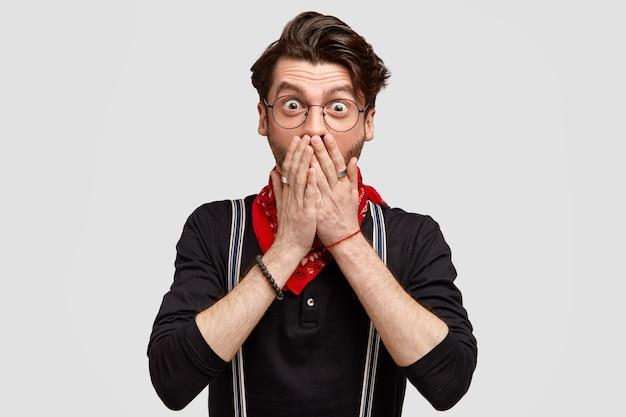 Das porträt eines verblüfften, stilvollen, gutaussehenden mannes sieht etwas angenehmes und unerwartetes, bedeckt den mund mit den händen und trägt ein modisches hemd