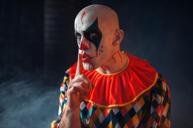 Das porträt eines verrückten blutigen clowns zeigt das ruhige zeichen