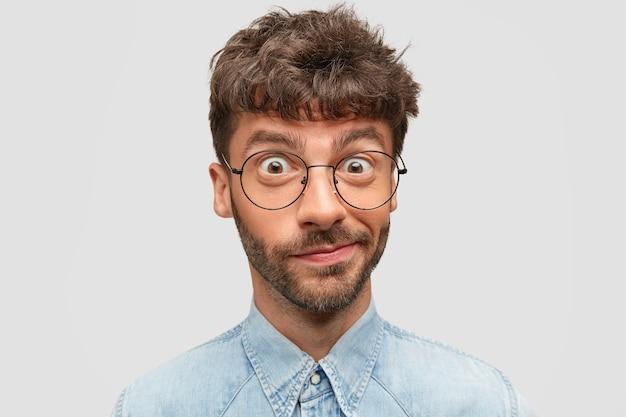 Das porträt eines zögernden mannes spitzt die lippen und sieht verwirrt aus, fühlt zweifel