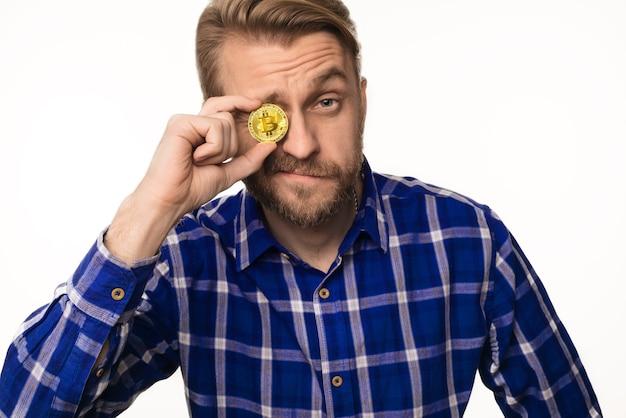 Das porträt eines zwinkernden mannes hält eine münze bitcoin vor seinem auge, das auf weiß isoliert wird