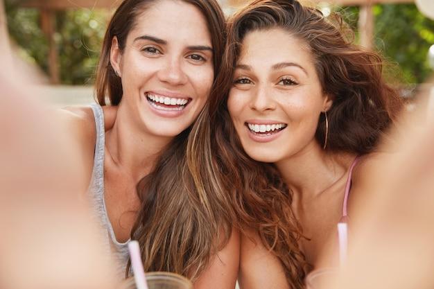 Das porträt glücklicher frauen hat ein breites lächeln und einen zufriedenen ausdruck, steht als pose für selfie nahe beieinander und wird fotos in sozialen netzwerken teilen