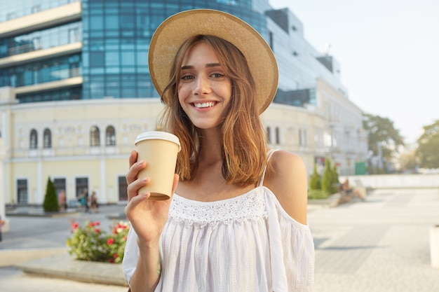 Das porträt im freien der fröhlichen attraktiven jungen frau trägt einen stilvollen hut, fühlt sich glücklich, steht und trinkt im sommer kaffee zum mitnehmen in der stadt