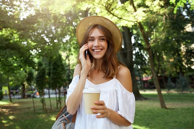 Das porträt im freien der fröhlichen charmanten jungen frau trägt einen stilvollen sommerhut und ein weißes kleid, fühlt sich entspannt, steht und trinkt kaffee zum mitnehmen auf der straße in der stadt