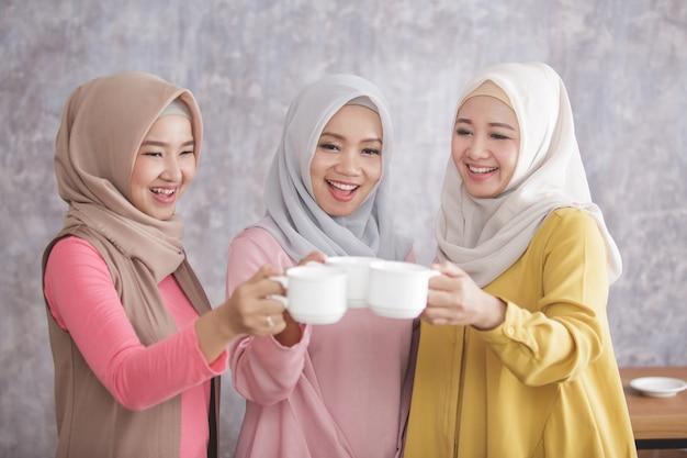 Das porträt von drei schönen muslimischen frauen jubelt ihrem kaffee zu, nachdem sie eine großartige arbeit und erfolg erzielt haben