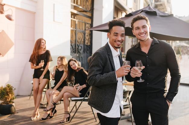 Das porträt von glückseligen frauen in trendigen kleidern sitzt auf stühlen mit gutaussehenden männern im vordergrund