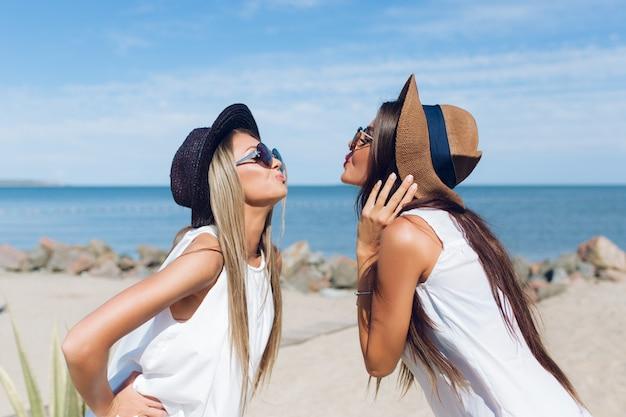 Das porträt von zwei attraktiven brünetten und blonden mädchen mit langen haaren steht am strand in der nähe des meeres. sie zeigen einen kuss.