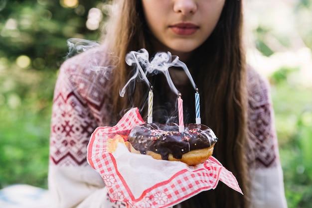 Das porträtiermädchen, das schokoladendonut mit hält, löschen kerzen aus