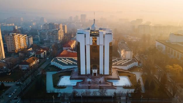 Das präsidentschaftsgebäude bei sonnenaufgang in chisinau, moldawien. nebel in der luft, kahle bäume, gebäude, straßen.