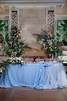 Das präsidium des brautpaares im festsaal des restaurants ist mit kerzen und grünpflanzen geschmückt, glyzinien hängen von der decke