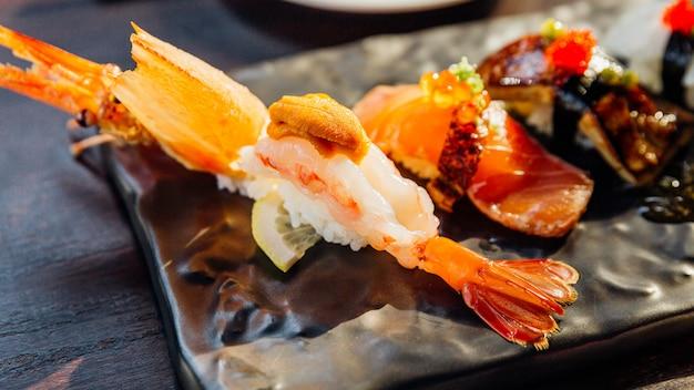 Das premium sushi set beinhaltet frittierte garnelen mit seeigel, foie gras, lachs und engawa auf der black stone platte, serviert mit wasabi und rosa eingelegtem ingwer. nahaufnahme auf garnelen-sushi.