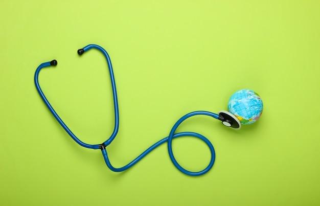 Das problem der globalen pandemie. stethoskop und globus an der grünen wand globale epidemie. draufsicht