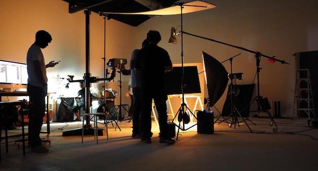 Das produktionsteam dreht einen videofilm für eine fernsehwerbung mit studioausrüstung.