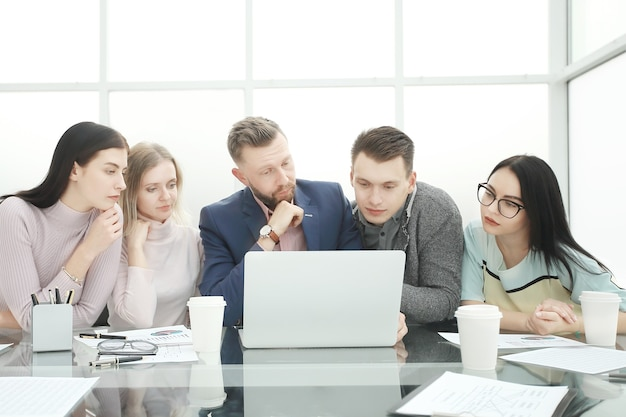 Das professionelle business-team schaut sich den laptop-bildschirm genau an