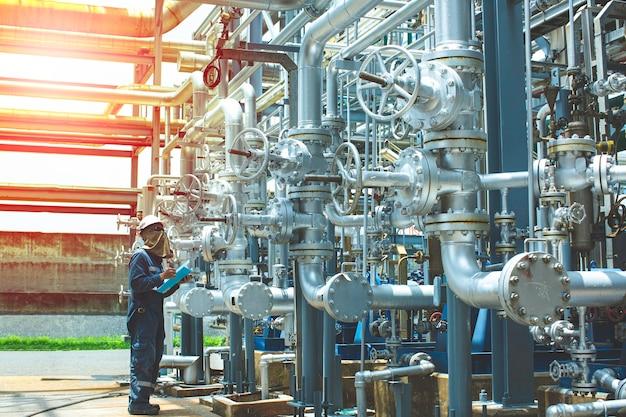 Das profil des männlichen arbeiters überprüft das anziehen des ventils und die verwendung von aufzeichnungen, während die raffinerieanlagenausrüstung für pipeline-öl- und gasventile am selektiven drucksicherheitsventil der gasanlage verwendet wird