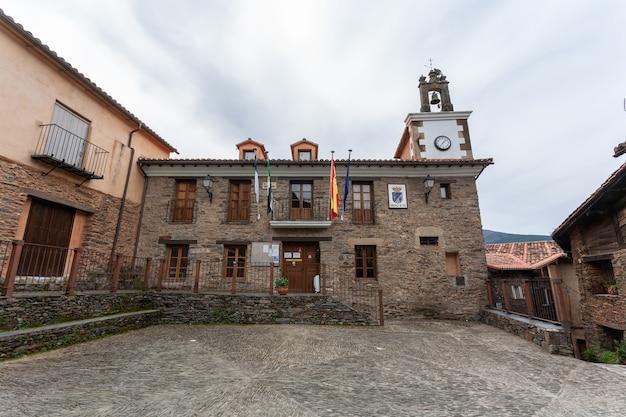 Das rathaus mit seinem uhren- und glockenturm mit den auf dem platz wehenden institutionellen fahnen