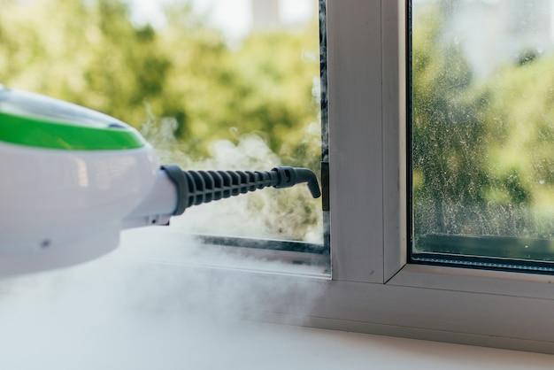 Das reinigungsgerät bläst einen dampfstrahl in den fensterrahmen.