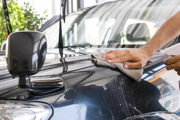 Das reinigungspersonal benutzt einen lack und ein mikrofasertuch, um den körper eines autos zu reinigen.