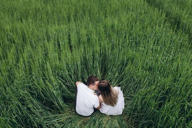 Das reizende paar in der liebe, die auf dem feld sitzt