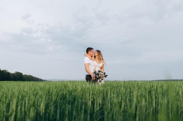 Das reizende paar in der liebe, die blumenstrauß umfasst und hält