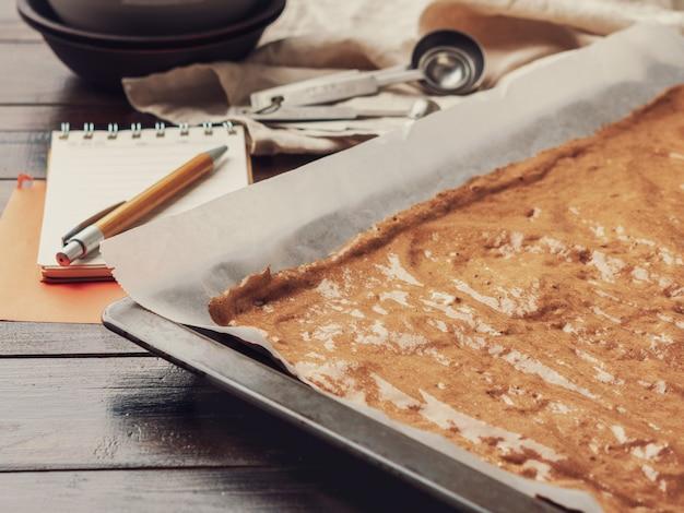 Das rezept für das kochen von selbst gemachten kuchen in der unterseite des backblechs auf hölzernem hintergrund.