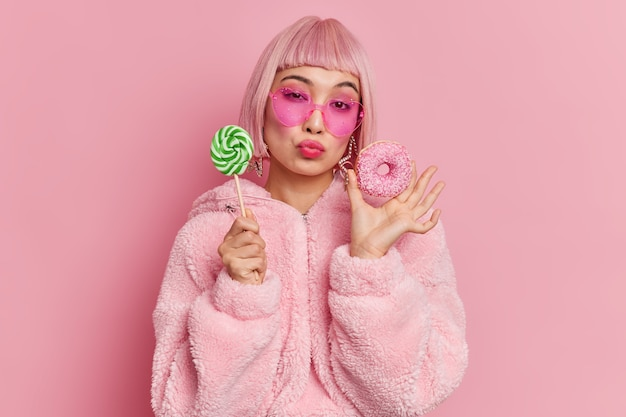 Das romantische, modische, weibliche model mit rosa haaren und glamour hat einen süßen lutscher und einen glasierten donut, gekleidet in eine trendige, herzförmige sonnenbrille mit warmem pelzmantel
