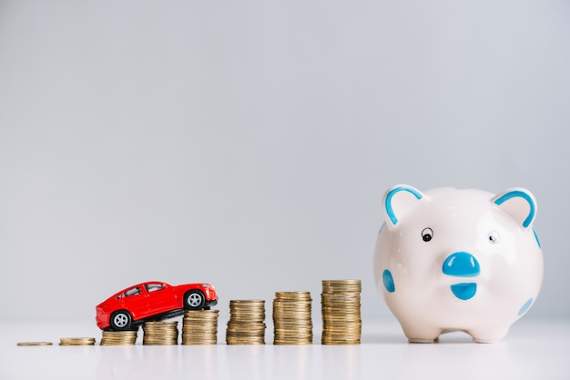 Das rote auto, das über das erhöhen der gestapelten münzen fährt, nähern sich piggybank