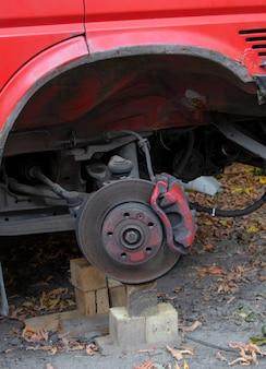 Das rote auto mit den ausgebauten radbremsen an einem auto ohne radbremsreparatur