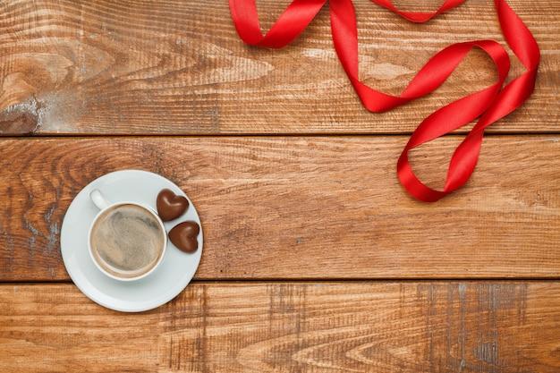 Das rote band, kleine herzen auf hölzernem hintergrund mit einer tasse kaffee