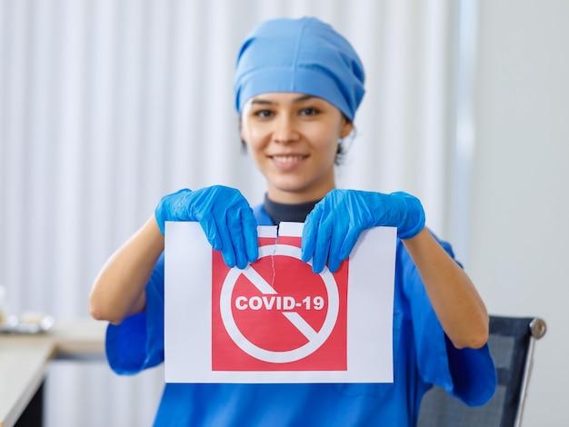 Das rote covid-19-papierschild wurde von einem glücklichen, schönen arzt in blauer krankenhausuniform auf verschwommenem hintergrund zerrissen, als die coronavirus-pandemie beendet war und das normale leben und das geschäft die sicherheit geöffnet haben