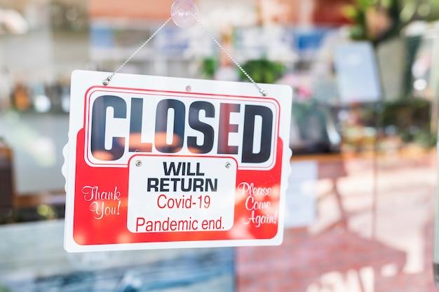 Das rote geschlossene schild am café-restaurant oder geschäftssitz des geschäftseingangs ist aufgrund der auswirkungen der coronavirus covid-19-pandemie geschlossen