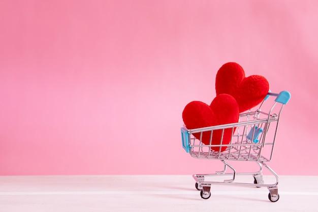 Das rote herz formt im einkaufswagen auf süßem rosa