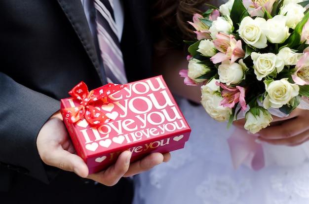 Das rote kästchen mit liebe in den händen des bräutigams