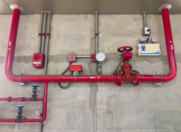 Das rote metallrohr und das große ventil des feuerlöschsystems in der nähe der betonwand des bahnhofs in der stadt, vorderansicht für den kopierraum.