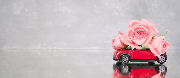 Das rote spielzeugauto, das blumenstrauß der rosarose liefert, blüht auf grauem hintergrund.
