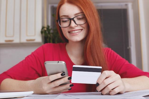 Das rothaarige hübsche weibliche modell in der brille hält smartphone und kreditkarte