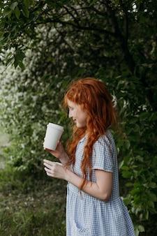 Das rothaarige kleine mädchen trinkt tee aus einem papierglas in einem apfelgarten.