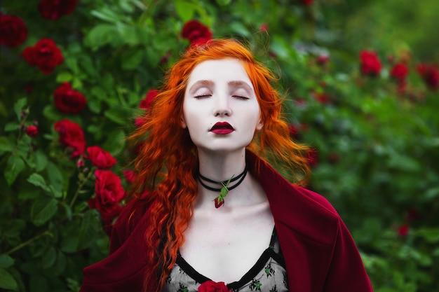 Das rothaarige mädchen im roten mantel, das auf einem hintergrund eines busches mit roten rosen aufwirft.